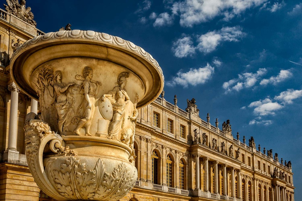 The Palace of Versailles near Paris, France photographed under warm, late afternoon light. A highly decorative piece stands out in front of the buildings magnificent facade.