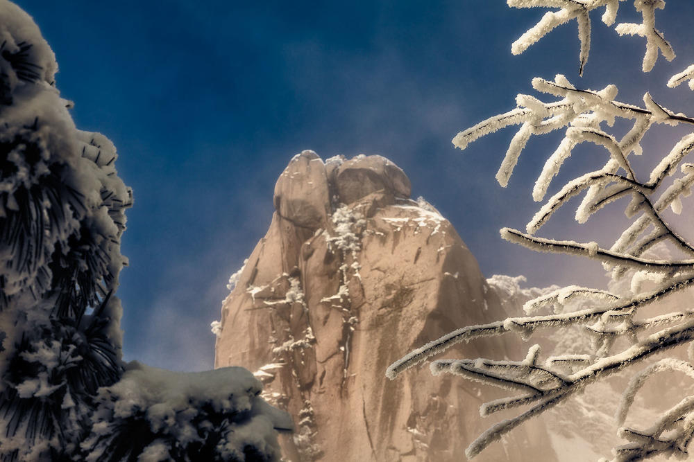A mountain peak, bathed in warm light, is framed by ice encrusted treees on the spectacular  Huangshan  (i.e., Yellow Mountain) in  China .