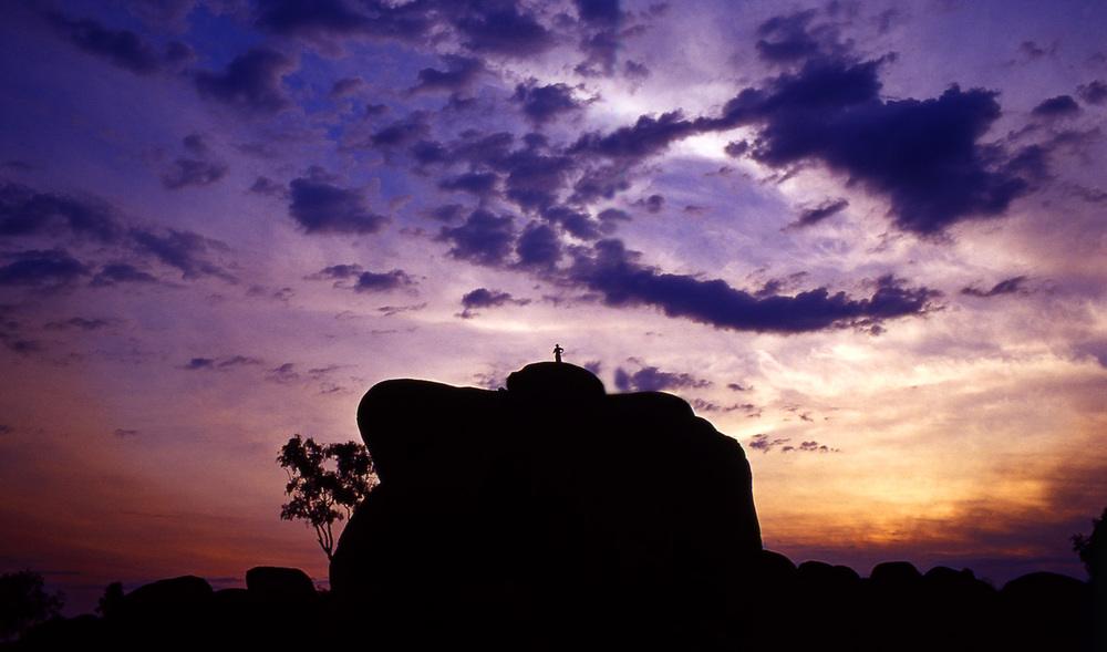 A tiny human figure on top of a huge bolder backlit by a wondrous sunset at Devils Marbles in Northern Australia.