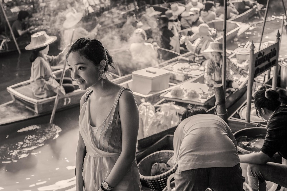 A young woman amidst the hustle and bustle of the floating market near Bangkok in Thailand.