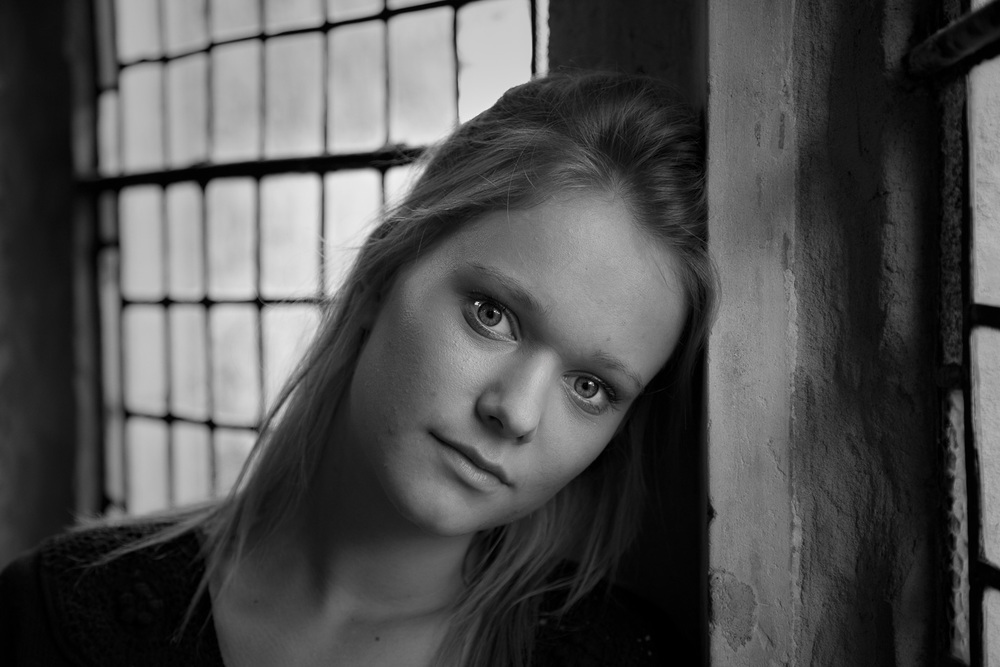 Lovely, delicate black and white portrait of young woman by window light.