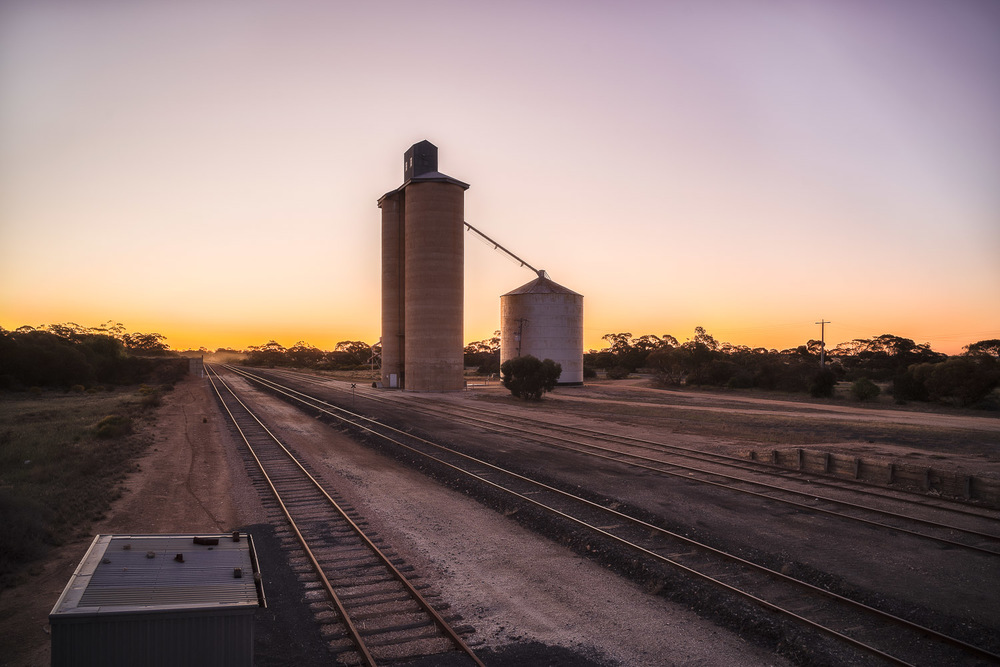 The  afterglow  provides a soft, delicate quality of light to this scene over looking train lines and silos at  Cowangie , Australia.