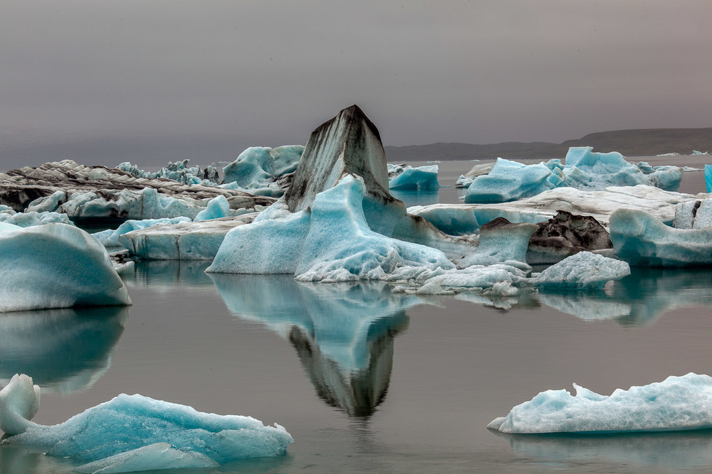 Large icebergs create stunning formations and a beautiful reflection on the Jokulsarlon Glacier Lagoon in Iceland.