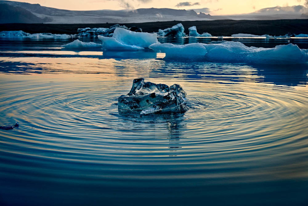 Ripples create a series of concentric patterns, surrounding floating ice, on the surface of the Jokulsarlon Glacier Lagoon, Iceland.