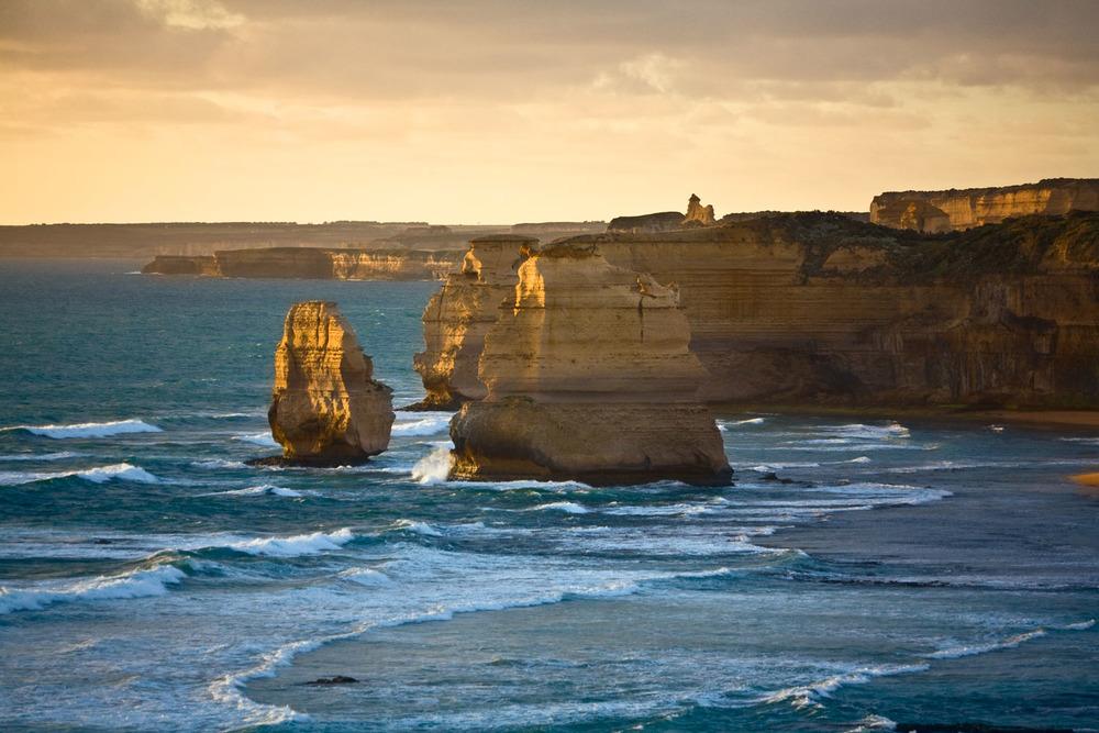 Warm light during the golden hour caresses the famous Twelve Apostles along Australia's Great Ocean Road.