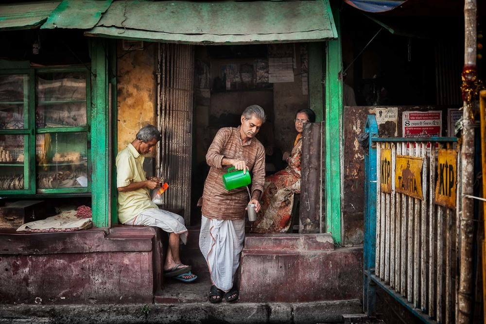 A candid image of a merchant pouring a cup of tea form a green jug in front of his establishment in Kolkata, India.