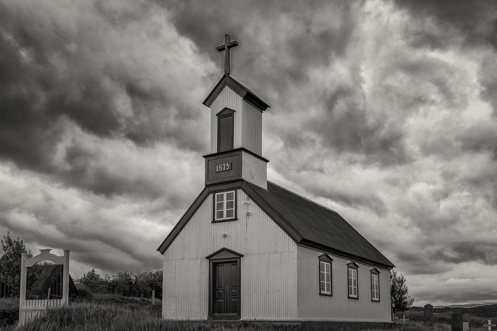 An  historic church  with an approaching  storm overhead ,  Southern Iceland