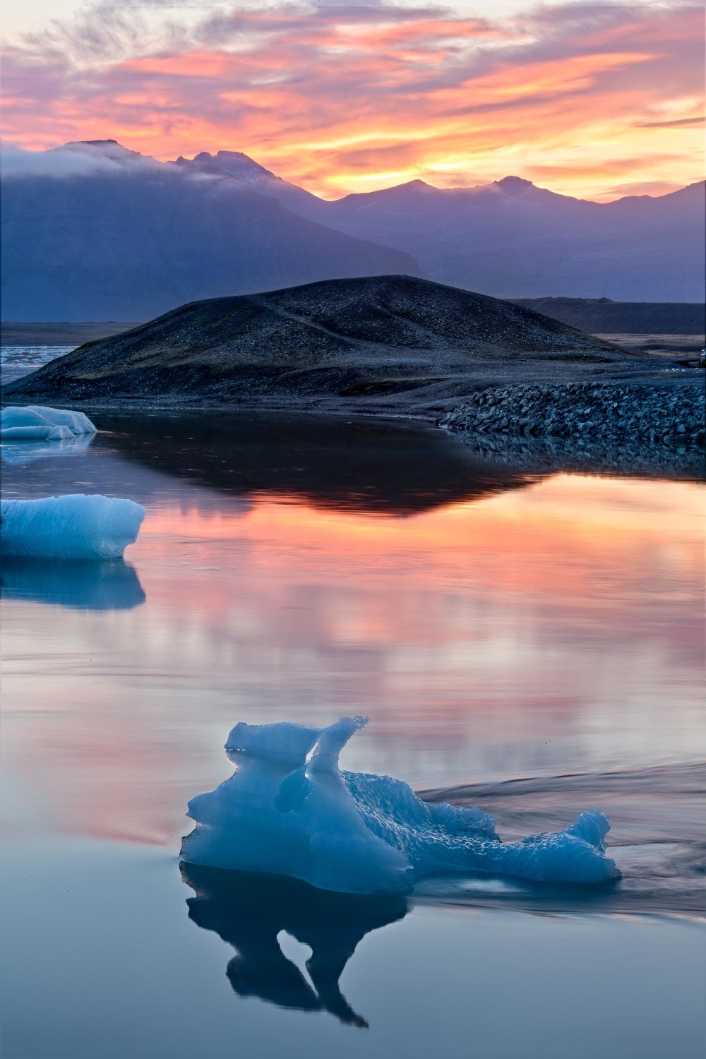 The serenity was palpable as the sun set on  Jokulsarlon Glacier Lagoon in Iceland . The contrasting warm of the sunset and the cool blue of the iceberg and lagoon provided a striking contrast.