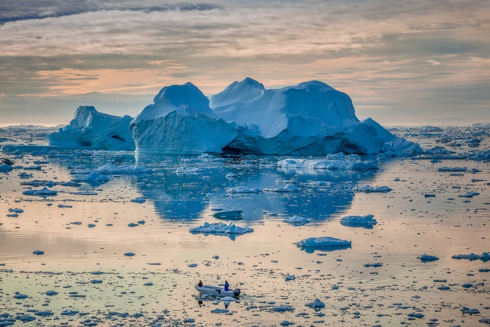 Two fisherman head out, under the midnight sun, into the wilds of the spectacular Ilulissat Icefjord in Ilulissat, Greenland.