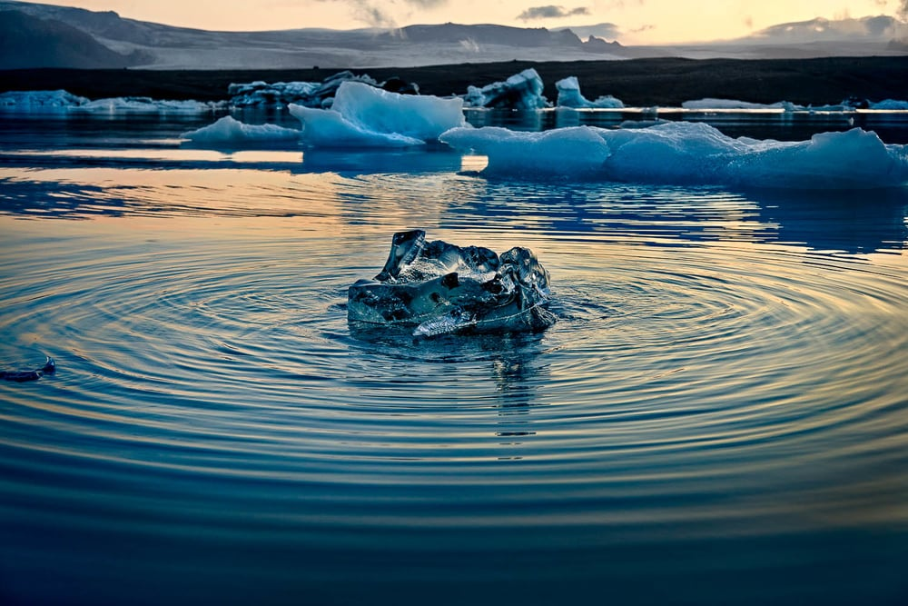 Ripples create a series of    concentric patterns   , surrounding    floating ice   , on the surface of the    Jokulsarlon Glacier Lagoon, Iceland   .