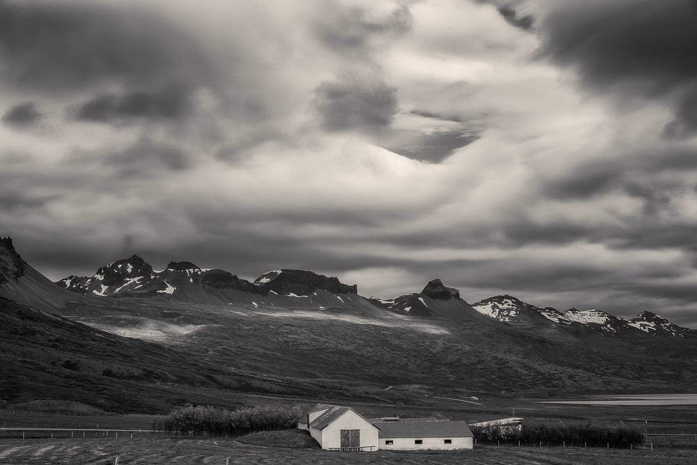 Farm buildings set amidst a beautiful landscape and a stormy sky in rural Iceland.