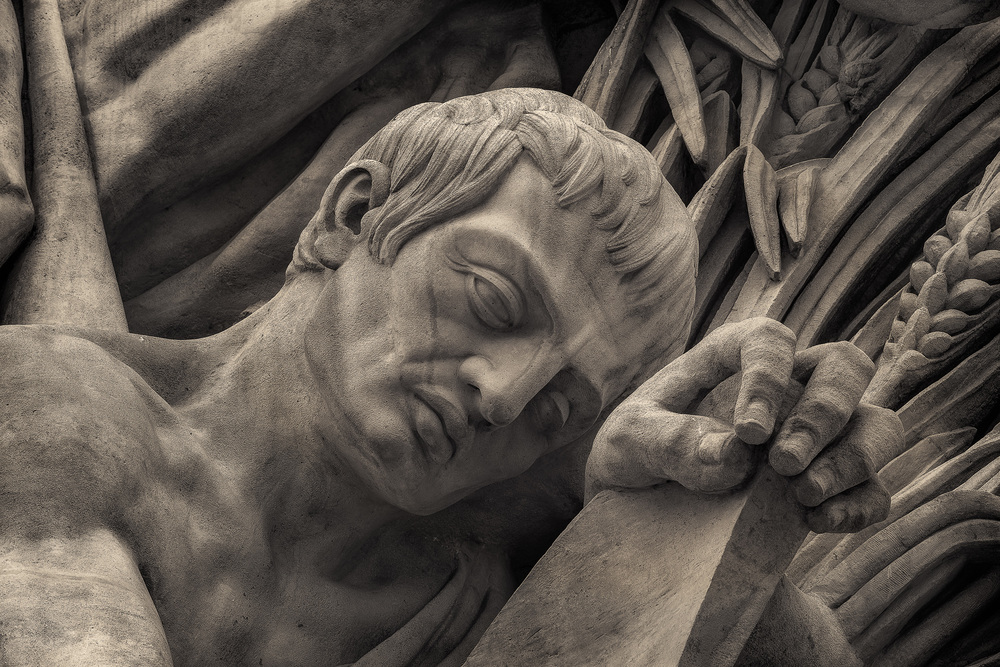 A  forlorn figure , carved in stone, at the base of the  Arc de Triomphe  in  Paris, France .