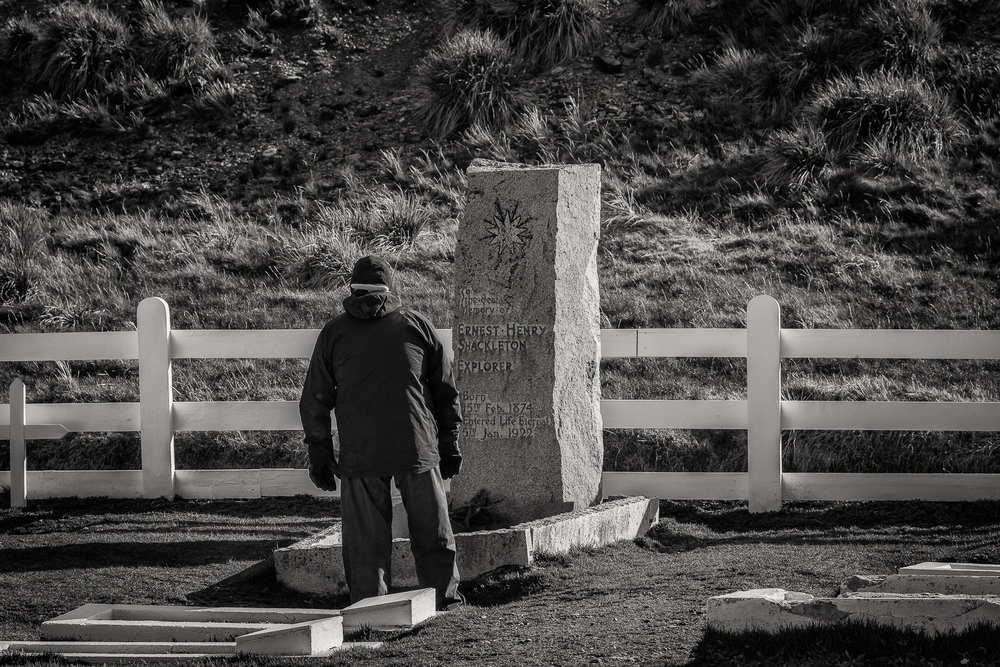 A tourist pays respects at the grave of explorer    Sir Ernest Shackleton    at    Grytviken    on    South Georgia Island   .