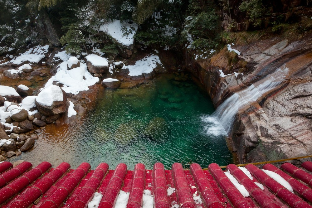 A colorful view, over a pagoda rooftop, down onto a tranquil pool fed by a small waterfall near  Huangshan, China .