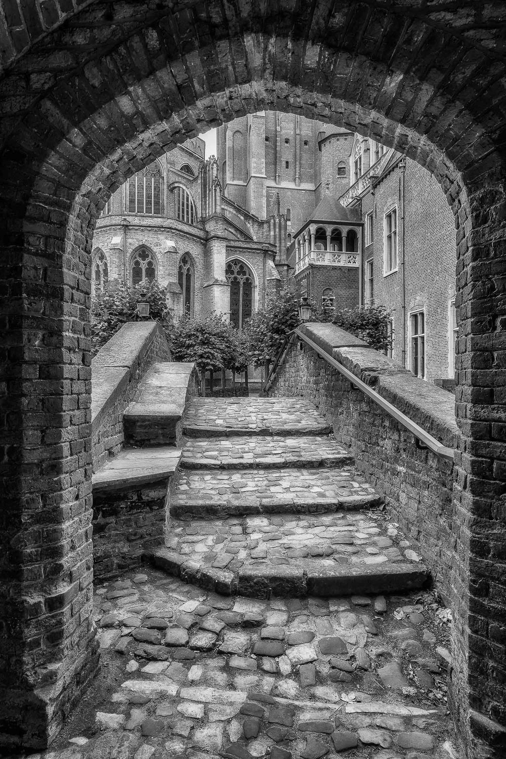 A classic view looking through an archway onto a bridge and onwards towards historic buildings in Bruges, Belgium.