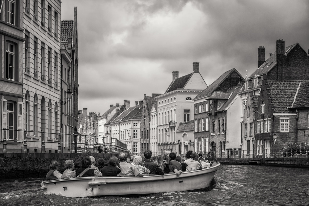 A group of tourists taking a small boat tour on the canal in    Bruges, Belgium   .