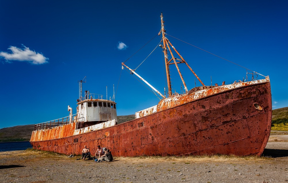 A surreal scene showing some local folk enjoying the sunshine, in front of a    beached ship   , on a beautiful summer's day in    northern Iceland   .