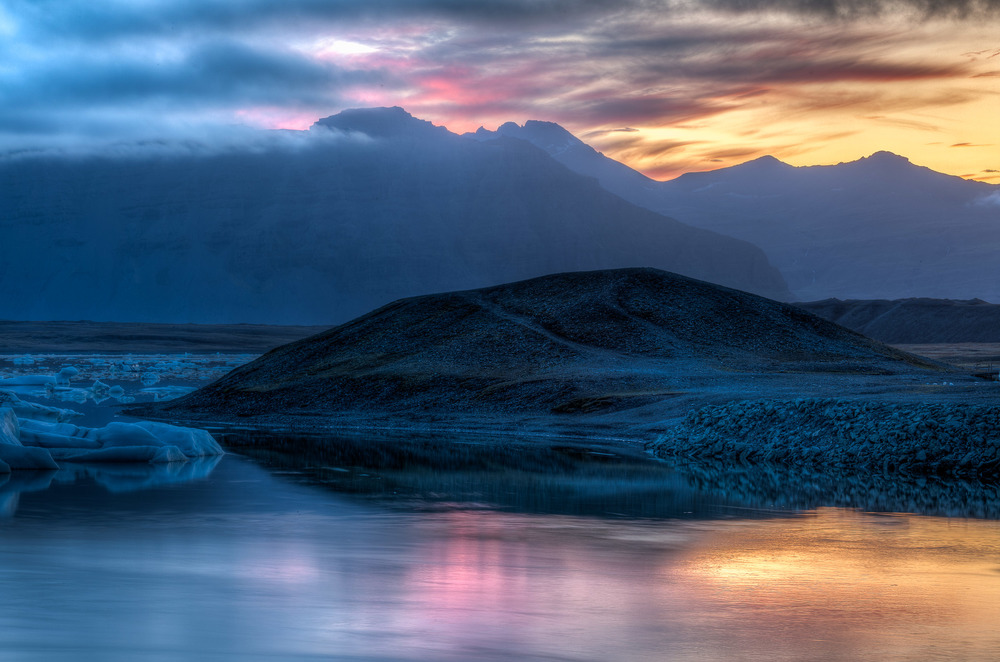 A beautiful glow at    sunset    illuminated the sky and water with a myriad of color at    Jokulsarlon Glacier Lagoon    in    Iceland   .