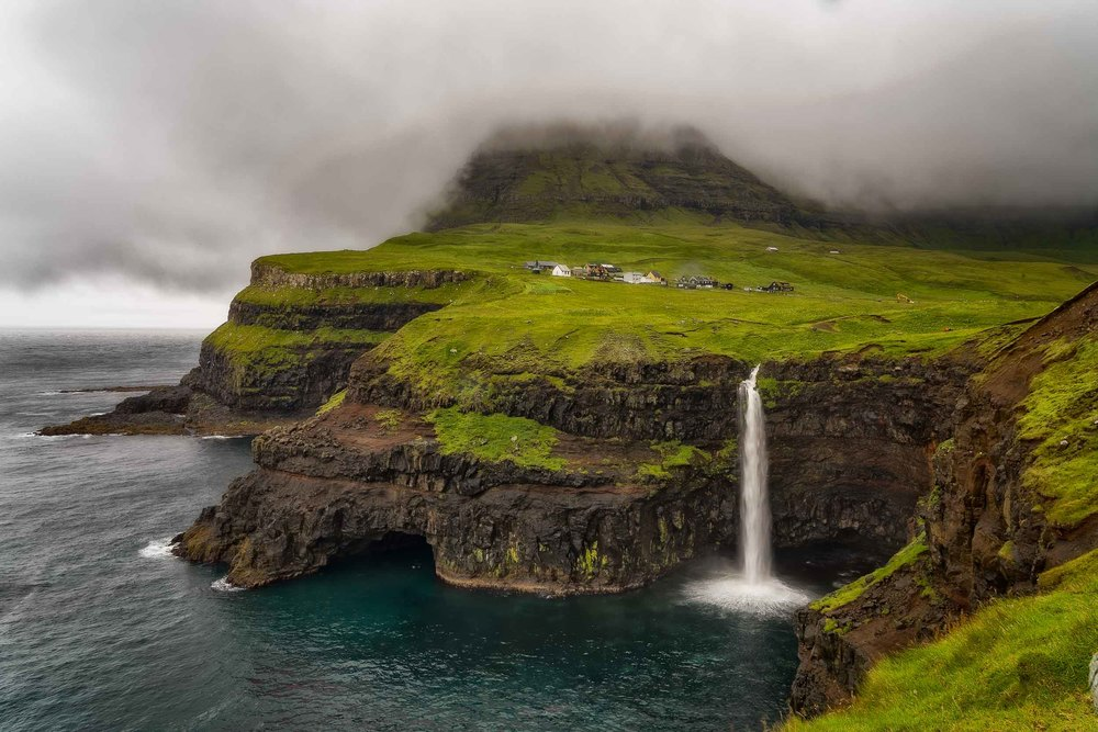 The spectacular  Gásadular Waterfall  on the edges of the sea on the island of  Vágar  on the  Faroe Islands .