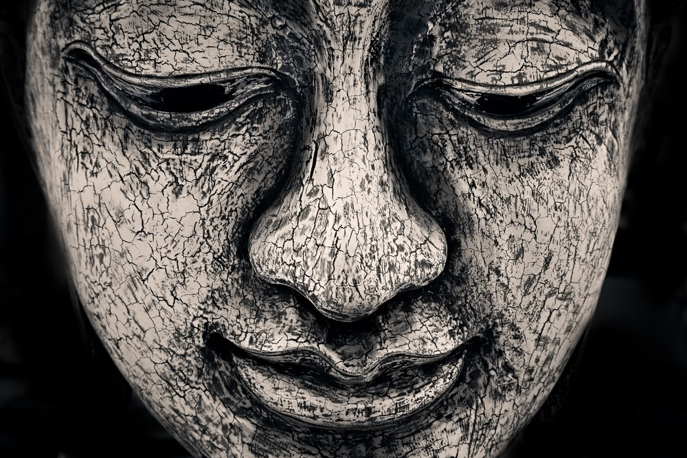 A detailed view of a    contemplative study of the Buddha's face    in this stone statue in rural    Thailand   .