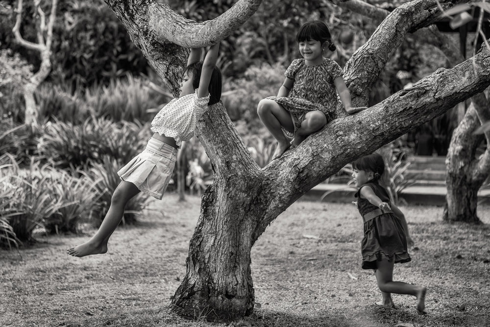 Three young girls at play in the grounds of a Hindu Temple complex in Bali, Indonesia.