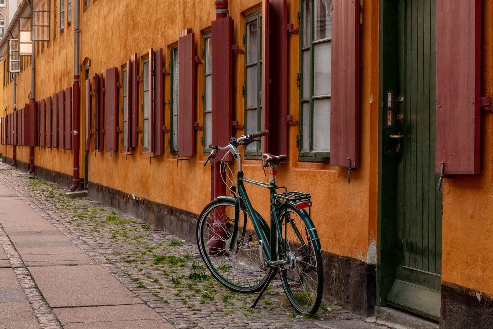 A bicycle parked alongside a colorful door and wall in an old part of Copenhagen, Denmark.