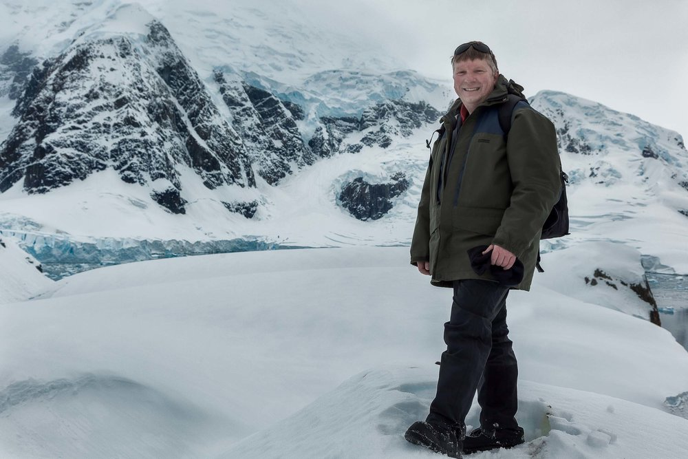 A photo of  Glenn Guy , the  Travel Photography Guru , on top of a hill above  Paradise Harbour  in  Antarctica .