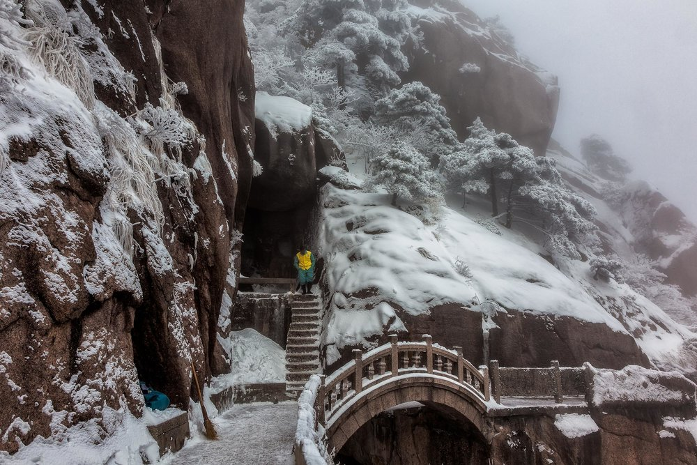 A  worker , with the job of sweeping the mountain trails of  Huangshan  free of  ice and snow , descends from a break and prepares to, once again, face the elements.