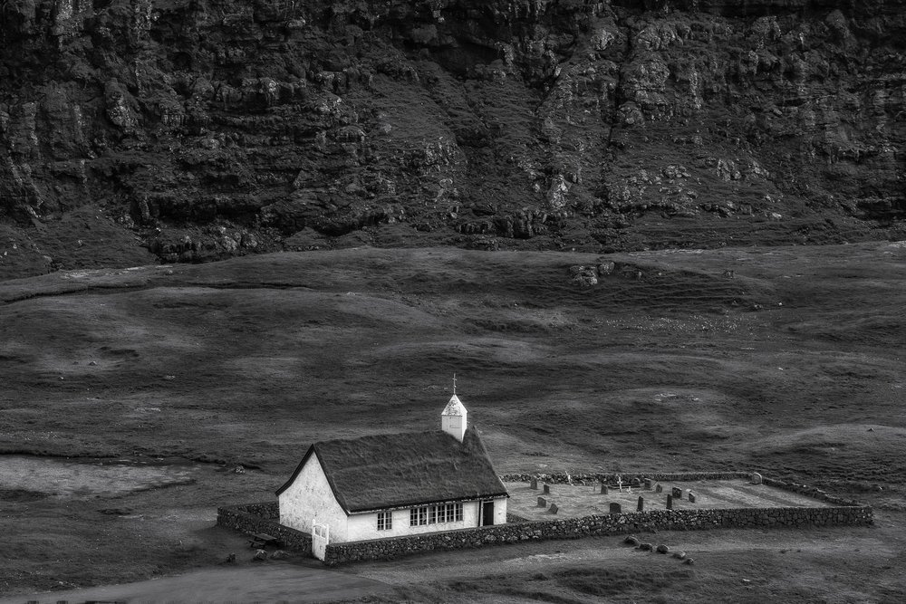 A    church and graveyard    stand alone in a beautiful field in the tiny village of    Saksun    on the north west coast of    Streymoy    in the    Faroe Islands   .