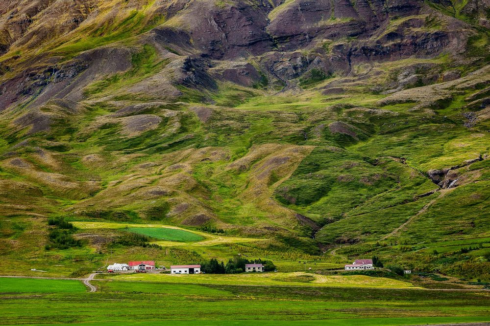 A dramatic mountain backdrop dwarfs a    tiny hamlet   , set amidst lush pastures, in rural    Iceland   .