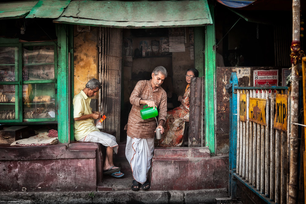 A candid image of a merchant pouring a cup of tea from a green jug in front of his establishment in Kolkata, India.