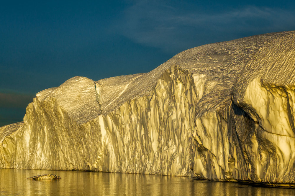 Golden light reflects off a    huge iceberg    during a Midnight Cruise on a long Summer's night on the    Ilulissat Icefjord in Disko Bay, Ilulissat, Greenland