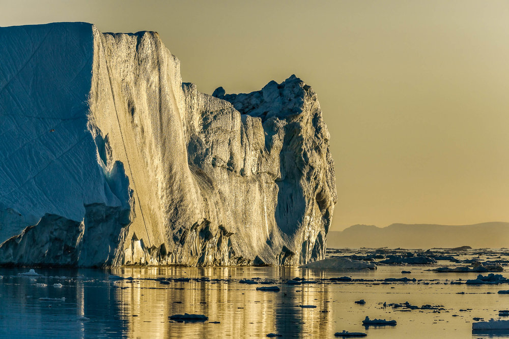 A giant iceberg photographed under the midnight sun on the  Ilulissat Icefjord  near the town of Iluliisat in  Western Greenland .