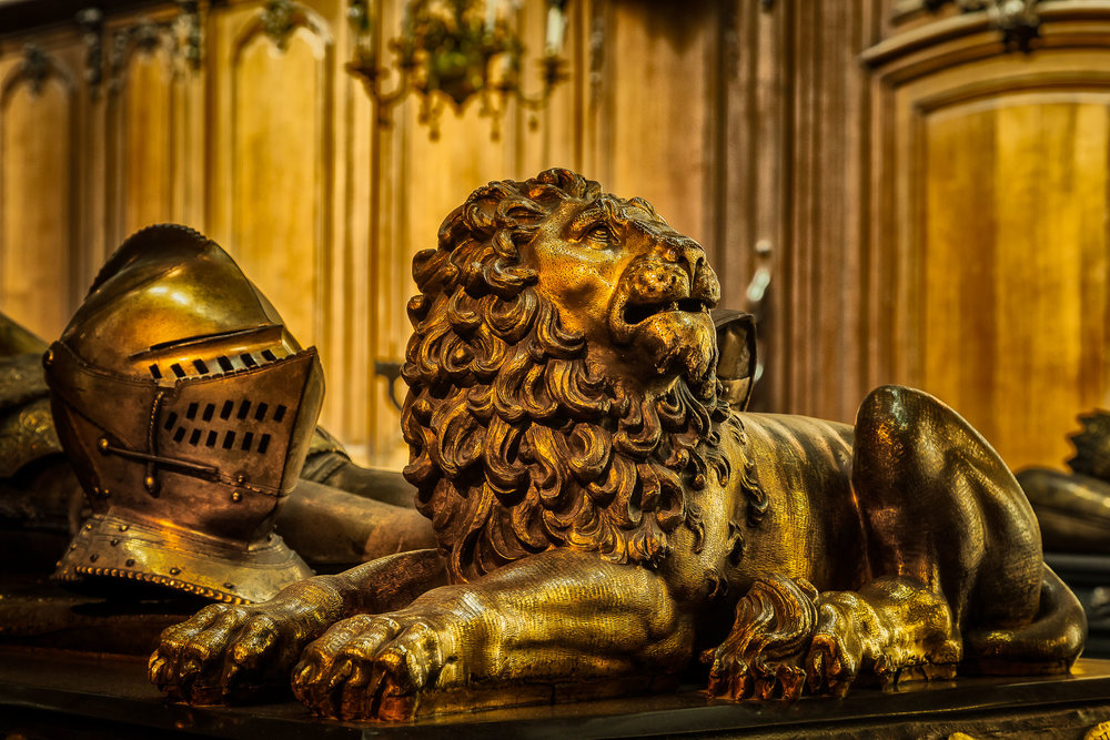A ornately carved statue of a lion on the tomb of Charles the Bold in the Church Of Our Lady, Brugge, Belgium. This image is a great example of monochromatic color.