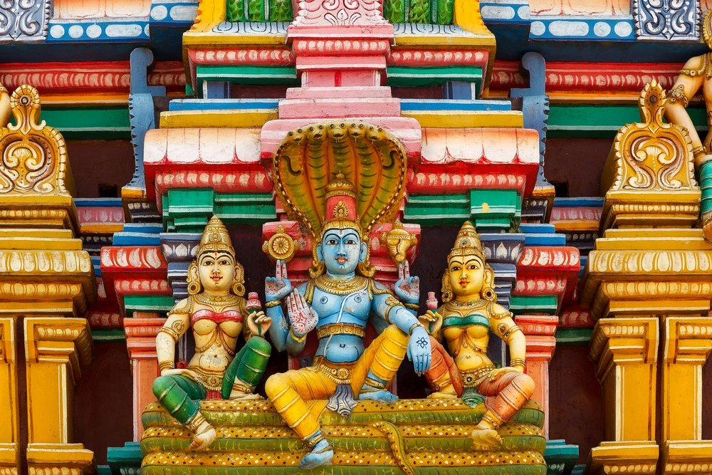 Garish colors reign supreme in this close up study of  Hindu deities  on the front of a shrine in  Chennai, India .