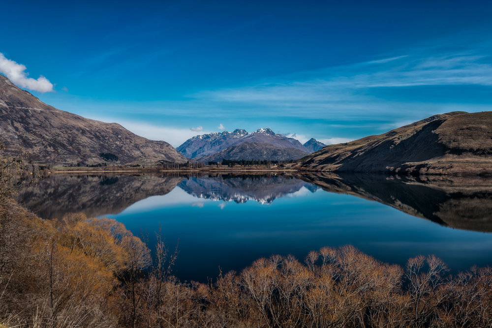 A stunning view on a beautifully clear day over Lake Hayes towards distant mountains, Otago, New Zealand.