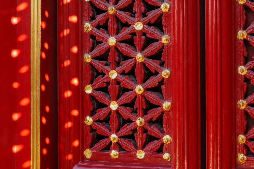 Light throws interesting shapes on a freshly painted window shutter in The Forbidden City in Beijing, China.