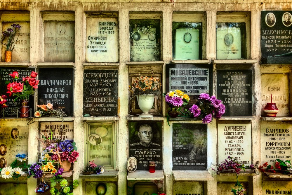 Tiny niche's holding plaques and flowers in the grounds of Novodevichy Cemetery in Moscow, Russia.