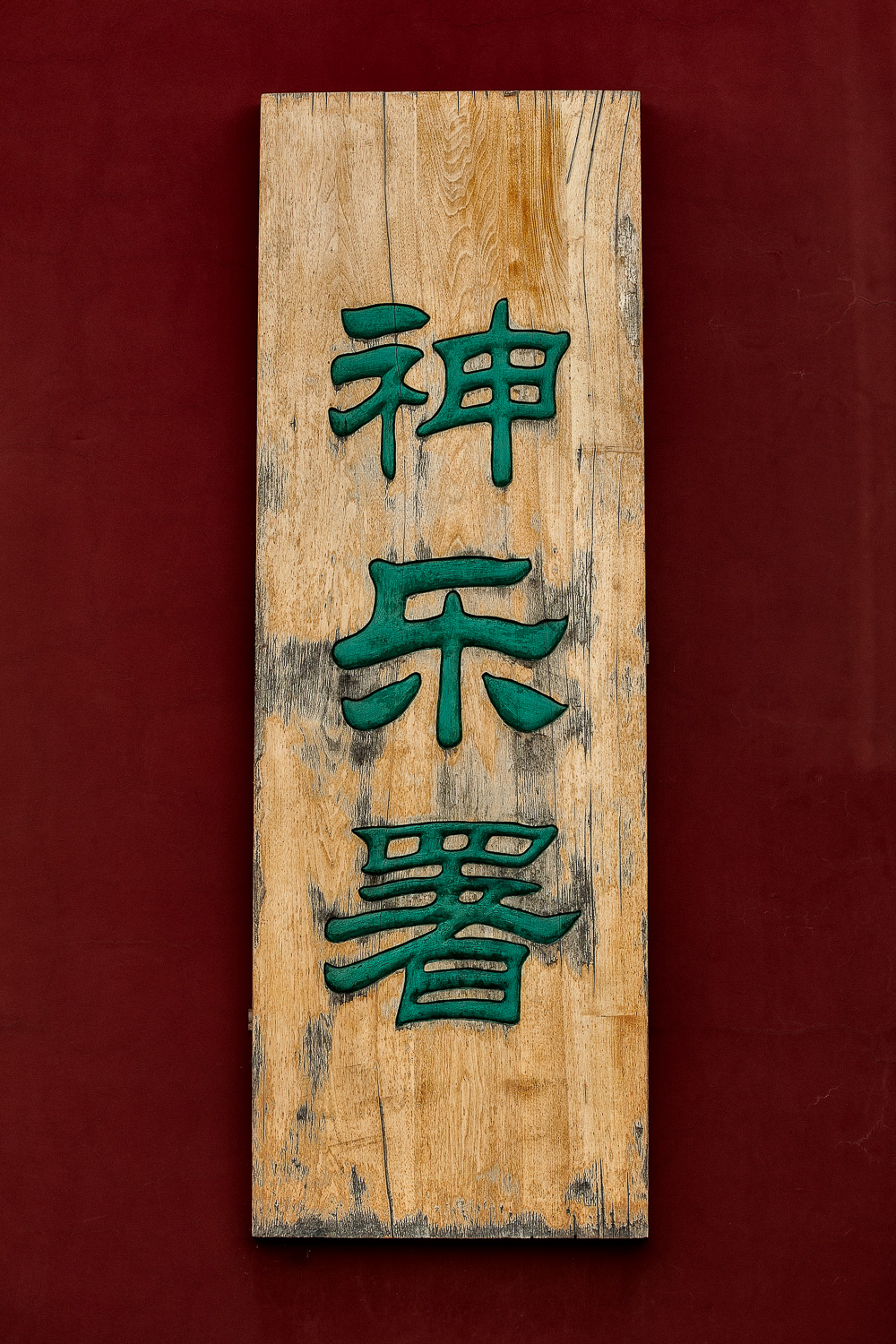 A beautiful, highly textured sign featuring vividly colored characters against a red wall in the grounds of the spectacular Temple of Heaven in Beijing, China.