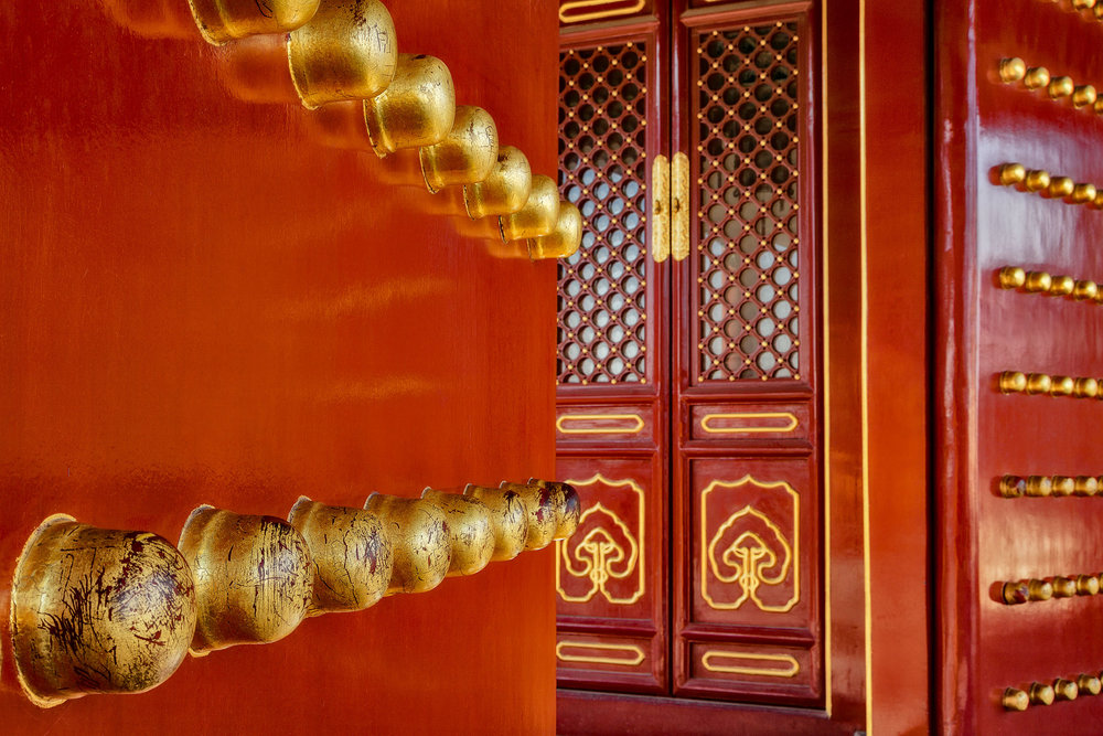 Large brass knobs lead the eye to a fabulously decorated door at the Temple Of Heaven in Beijing, China.