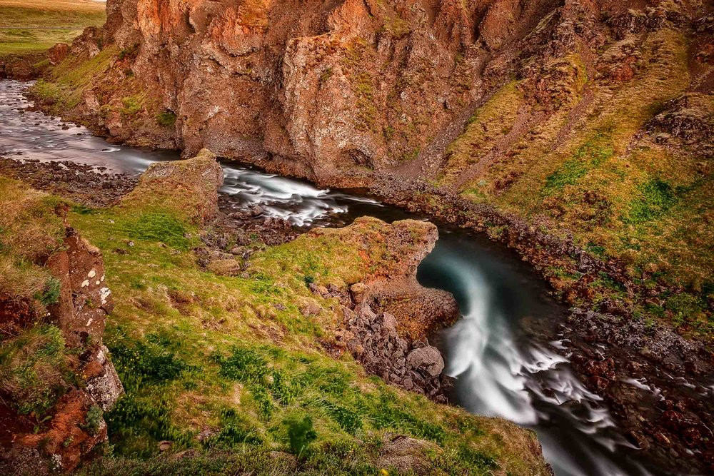 Soft, gentle light illuminates this scene of a fast flowing river cutting its way through a rocky landscape in Southern Iceland.
