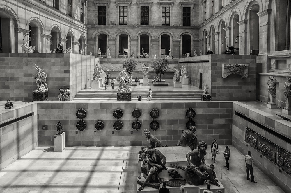 Visitors exploring an amazing space within the  Louvre museum in Paris, France . This image explores light, tone and shape to help tell the story.