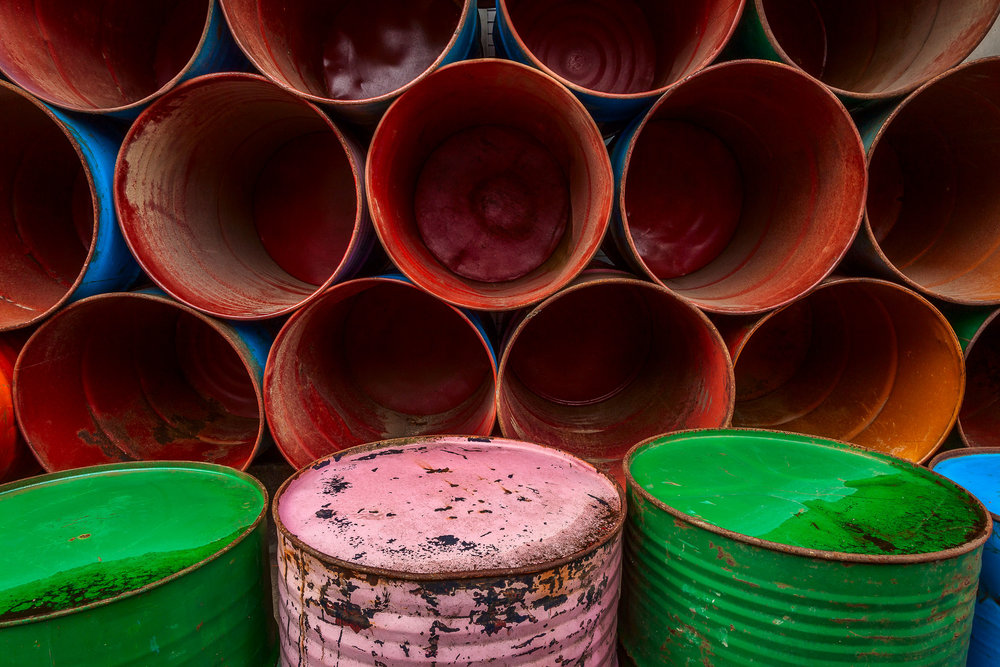 An arrangement of  colorful barrels , stacked by the side of the road in  Ubud, Bali  make for a  vivid and symmetrical composition .