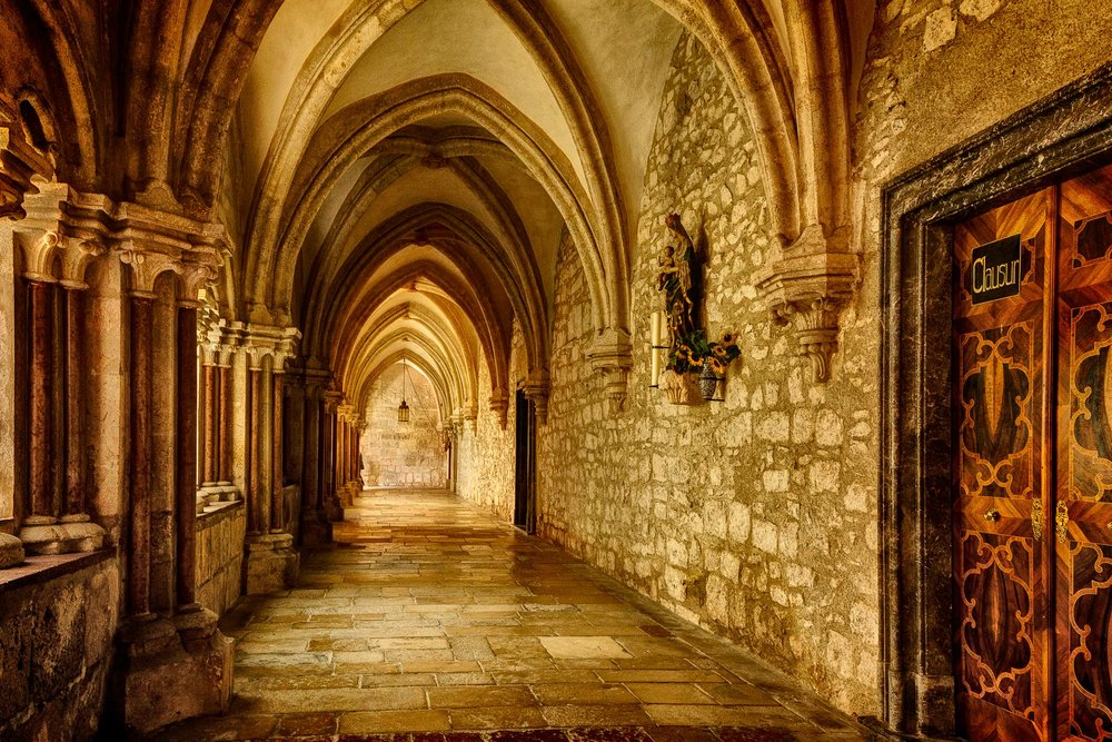 A view down a stone corridor at Helligenkreuz Abbey in Austria.