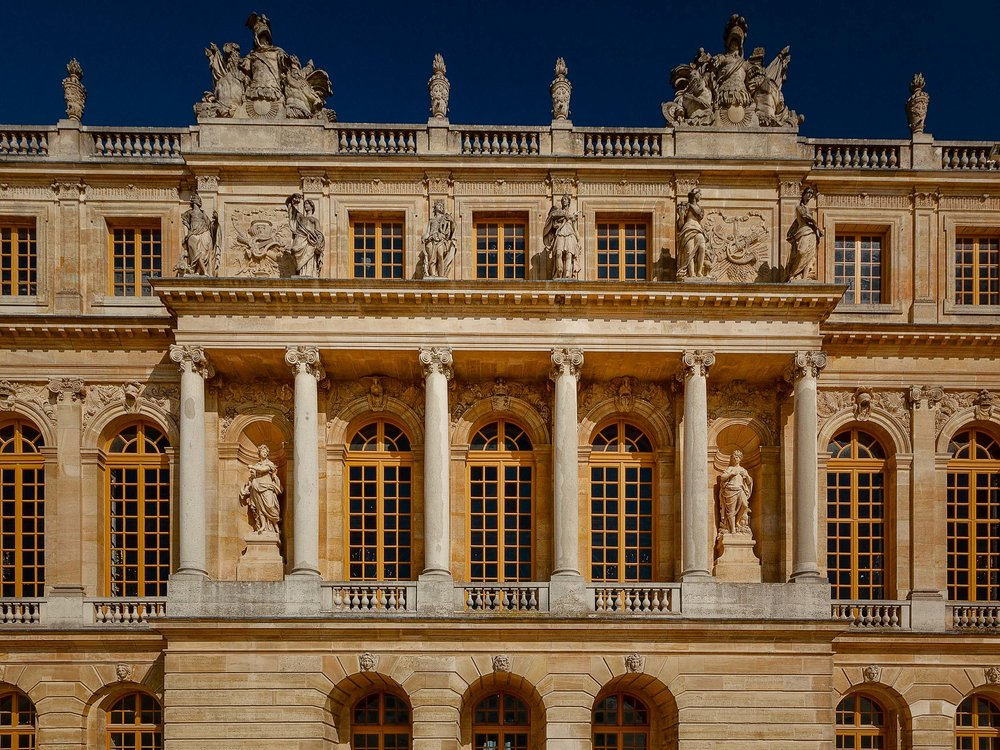 A detail of the  facade of Versailles , just out of Paris, France. The light was such that it brings out the  luminous quality of the gently textured stone  and the  shapely statues  within this beautifully  symmetrical building .