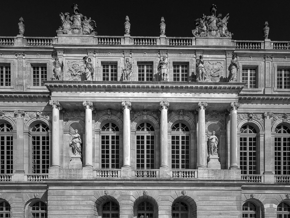 A  black and white detail  of the facade of  Versailles, France .