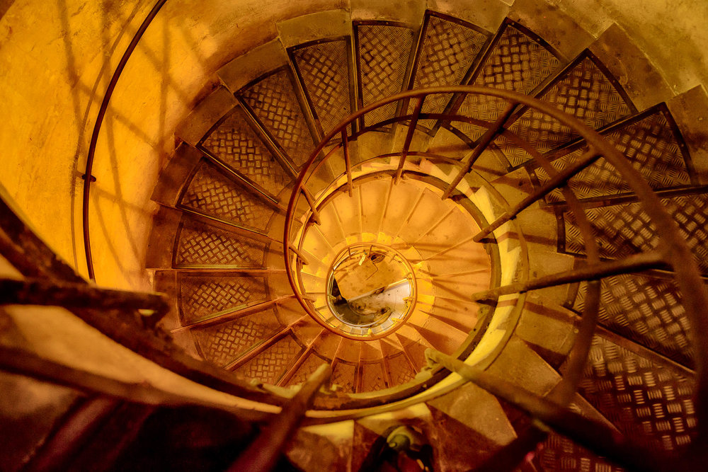Looking down a spiral staircase that descends from the top of the Arc de Triomphe in Paris, France.