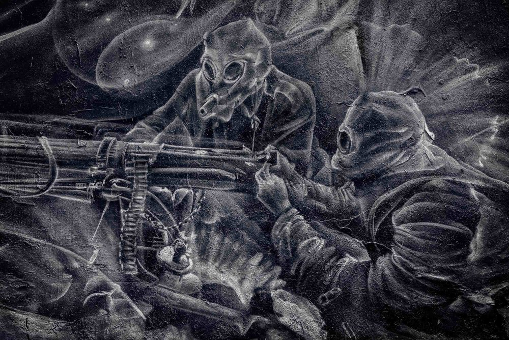 Street Art  showing a scene, possibly from  World War One , of  two soldiers in gas masks firing a machine gun .