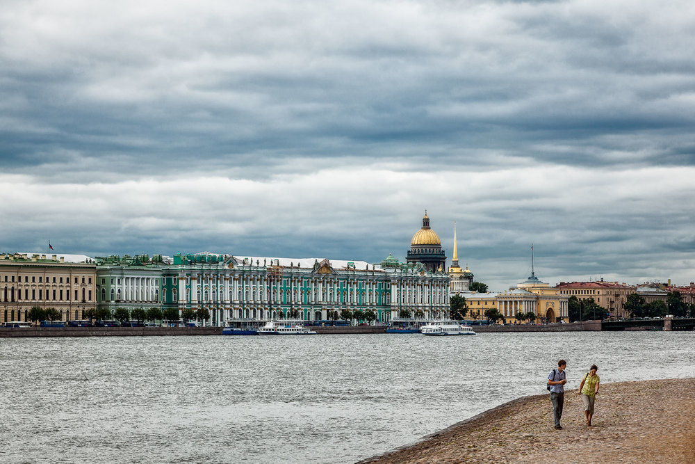 A couple walking by the shores of the River Neva, right in front of Peter and Paul Fortress in St. Petersburg, Russia.