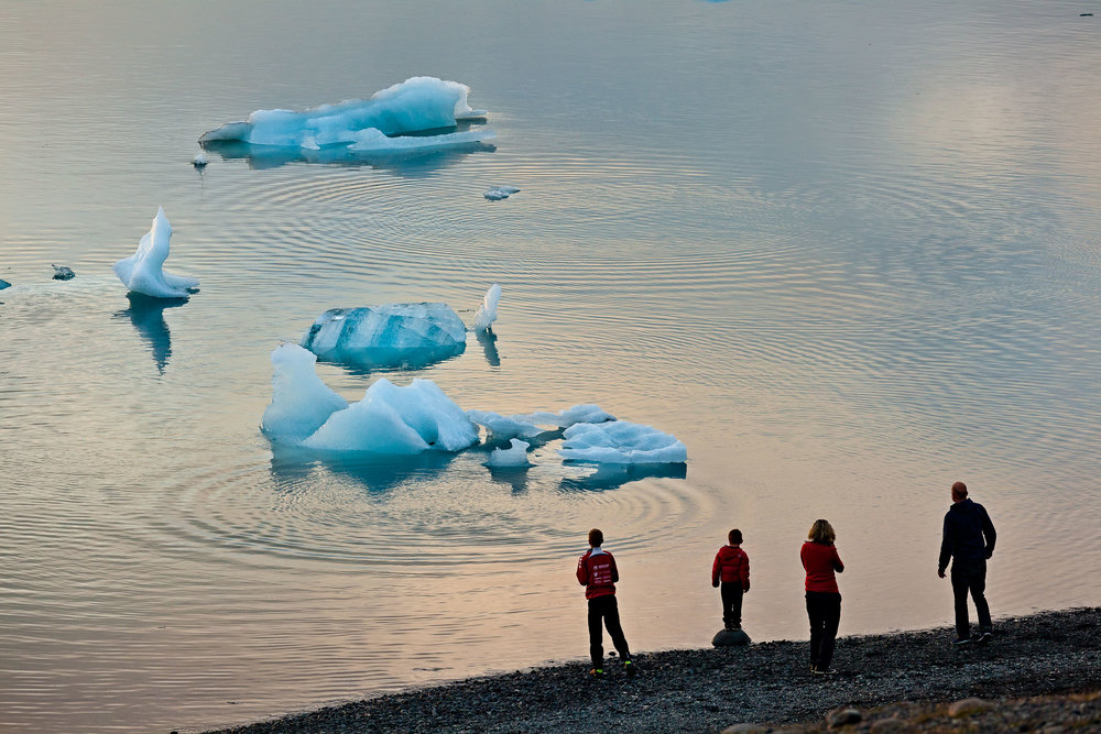 A  family  watching the  breaking up of an iceberg  from the shore of the incredible  Jokulsarlon Glacier Lagoon  in  Southern Iceland .
